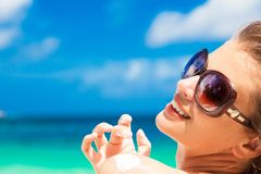 Close up of young woman in sunglasses putting sun cream on shoulder Royalty Free Stock Photos