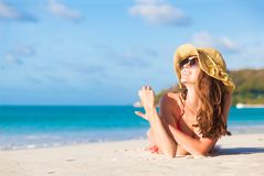 Long haired woman in bikini and straw hat lying on tropical beach royalty free stock photo