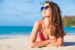 Long haired woman in bikini and sunglasses lying on tropical beach royalty free stock photo