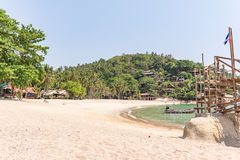 A remote tropical cove on a Thai island. Haad Sadet Beach, Koh Pangan, Thailand, April 26, 2016. A far-off bay with a few shacks Royalty Free Stock Image
