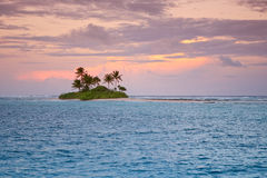 Remote Tropical Island at Sunset. With orange sky and blue ocean water Stock Image