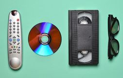 Remote from the TV, 3d glasses, CD drive, vhs on mint color pastel background. Retro technology.  Royalty Free Stock Image