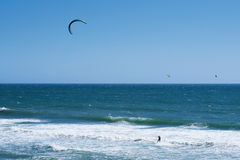 Remote view at kite surfers riding the waves Stock Image