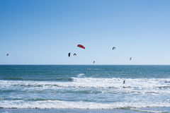 Remote view at kite surfers riding the waves Stock Photo