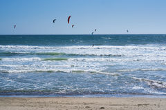 Remote view at kite surfers riding the waves Stock Photography