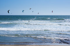 Remote view at kite surfers riding the waves Royalty Free Stock Photos