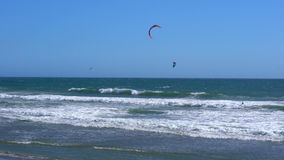 Remote view at kite surfers riding the waves stock video footage