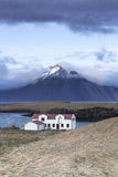Remote white Icelandic house on the shores of Atlantic ocean. Djupivogur, Iceland – May 27, 2015: White house in a fjord on the Atlantic ocean in the Icelandic Stock Photography