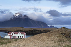 Remote white Icelandic house on the shores of Atlantic ocean. Djupivogur, Iceland – May 27, 2015: White house in a fjord on the Atlantic ocean in the Icelandic Royalty Free Stock Photo