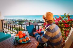 Remote work concept- young man with laptop on scenic terrace. Remote work concept- young man with laptop having breakfast on scenic terrace royalty free stock photo