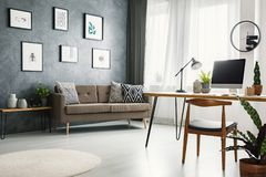 Remote work corner desk in living room interior with raw wall wi. Th posters, couch with pillows and window with drapes royalty free stock image