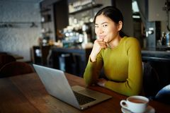 Remote work. Young Asian girl with laptop watching curious video in cafe by cup of drink Stock Images