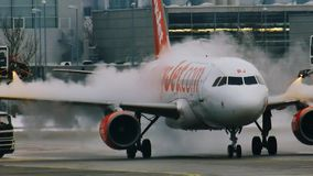 Remova o gelo do avião de Easyjet no aeroporto de Munich video estoque