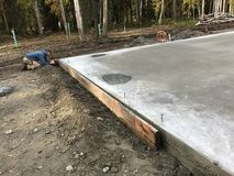 Removal of concrete form boards. Removing form boards from fresh concrete foundation Stock Image