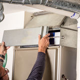 Removal of furnace access door for filter. Man removes the furnace filter cover to inspect Stock Image