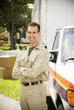 Removal man standing beside their van with packing boxes Stock Image