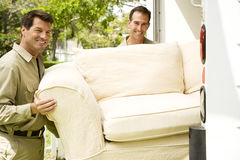 Removal men with sofa beside their van Royalty Free Stock Photography