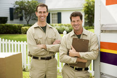 Removal men standing beside their van with packing boxes Stock Photography