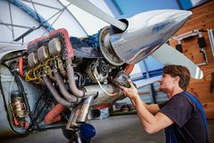 Replacing the defective parts of the aircraft service worker. Removal and repair of an engine starter of an airplane by a service worker royalty free stock image
