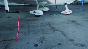 Remove before flight pitot tube cover on small general aviation airplane. Protection for air speed measuring instrument, red warning flag on aircraft, closeup stock video