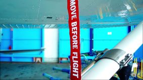 Remove before flight pitot tube cover on small general aviation airplane. Protection for air speed measuring instrument, red warning flag on aircraft, closeup stock footage
