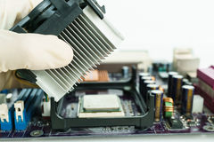 Remove heat-sink from board with hand. Remove heat-sink from mainboard with hand Royalty Free Stock Photography