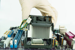 Remove heat-sink from board with hand. Remove heat-sink from mainboard with hand Royalty Free Stock Image