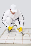 Remove old tile strike chisel. Worker removes old white tiles from floor with hammer and chisel stock images