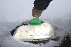 Remove snow from car lamp after Blizzard Royalty Free Stock Photos