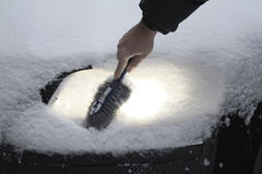 Remove snow from car lamp after Blizzard Stock Photography