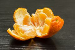 Peeled skin of ripe mandarin fruit and divided into parts. Stock Photo