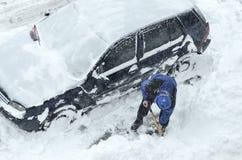 Removendo a neve dos carros imagens de stock royalty free