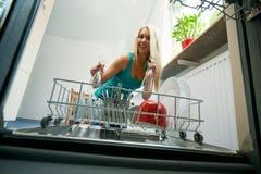 Removendo os pratos da máquina de lavar louça fotografia de stock royalty free