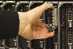 Removes hard drive. IT technician / consulant insert / remove a harddisk from a blade server data center. This is a 2,5 SAS harddrive royalty free stock photos