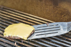 Removing A Cheeseburger From A Hot Grill Royalty Free Stock Photo