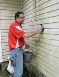 Removing Algae And Mold From Vinyl Siding. Worker removing algae and molf from a house with vinyl siding stock photo