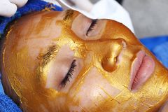 Anti Aging Facial with Golden Mask Cream massage. Removing Anti Aging Facial with Golden Mask Cream massage on woman face with device. Gold Flakes has collagen Royalty Free Stock Photos