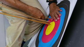 Removing arrows from target. Pulling out Arrows in archery target stock video footage