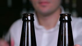 Removing the caps from bottles of beer closeup. The bartender opens a couple of bottles of beer stock footage