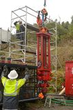 Removing the casing. MOANA, NEW ZEALAND, OCTOBER 27, 2017: Engineers discuss how to set up a huge hydraulic jack on top of an old oil well to remove the steel Stock Photo