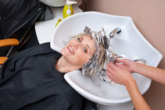 Removing coloring foil from hair. Stylist removing coloring foil from woman hair Stock Image