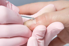 Removing cuticle from the nail Royalty Free Stock Images