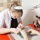 Removing cuticles. Caucasian female manicurist removing cuticles with nipper Stock Images