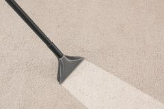 Removing dirt from carpet with vacuum cleaner. In room stock photo