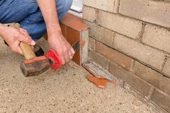 Removing external wall tiles. Man removing tiles from a door step with the aid of a hammer and bolster royalty free stock photos