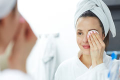 Removing eye makeup. Woman removing makeup with cotton pad Royalty Free Stock Images