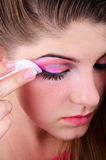 Removing Eyes Makeup. Young girl removing her eyes colorful makeup Stock Photo