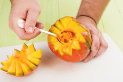 Removing flesh of pumpkin Royalty Free Stock Photo