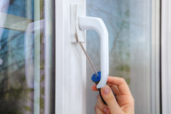 Removing handle of a plastic window using hand screwdriver. Dismantle the handle on a pvc window using a screwdriver, close-up of a hand with a tool stock photos