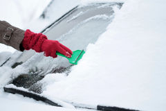 Removing ice and snow from windshield Royalty Free Stock Photo